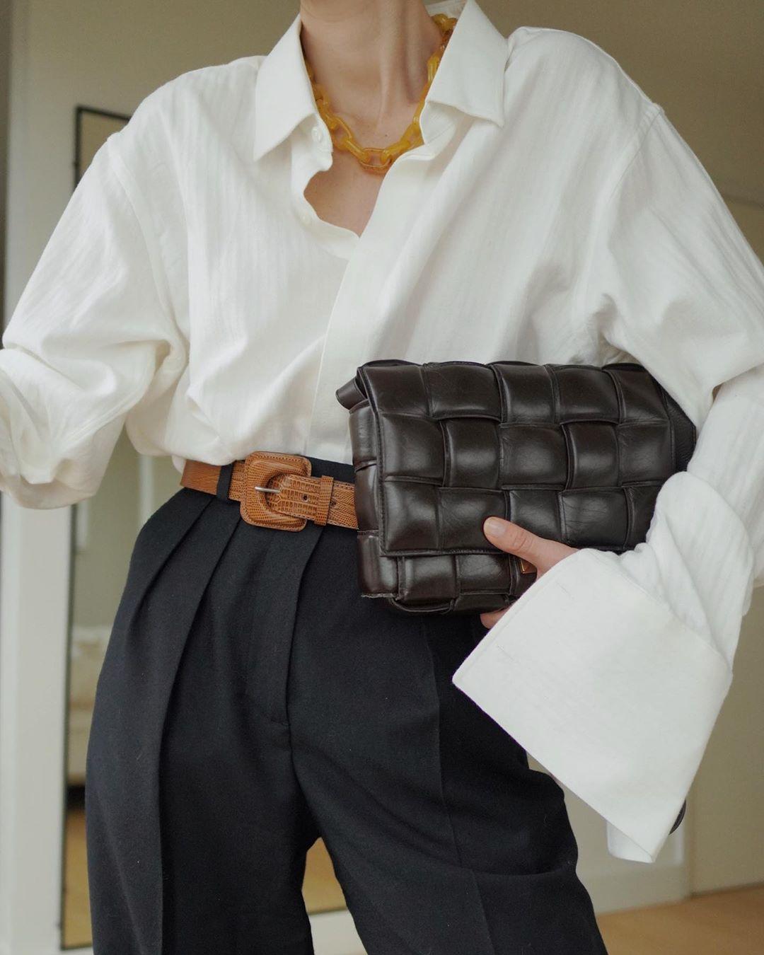cô gái mặc so mi trắng quần đen thắt lưng trắng đeo túi bottega veneta