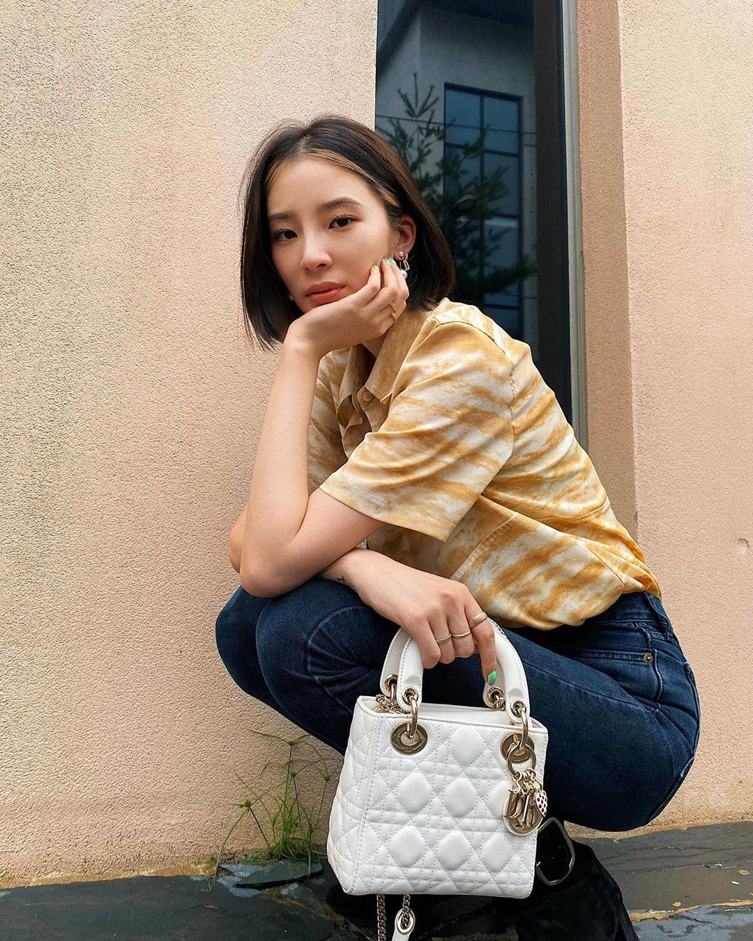 cô gái mặc áo vàng và túi lady dior trắng