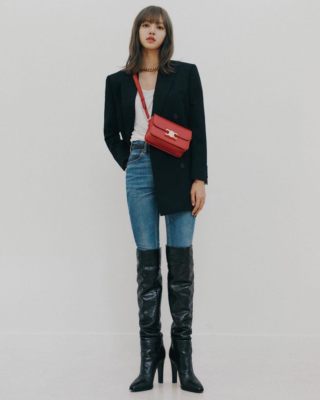 Lisa mặc áo trắng coat đen quần jeans xanh bốt cao cổ đeo túi celine triomphe đỏ