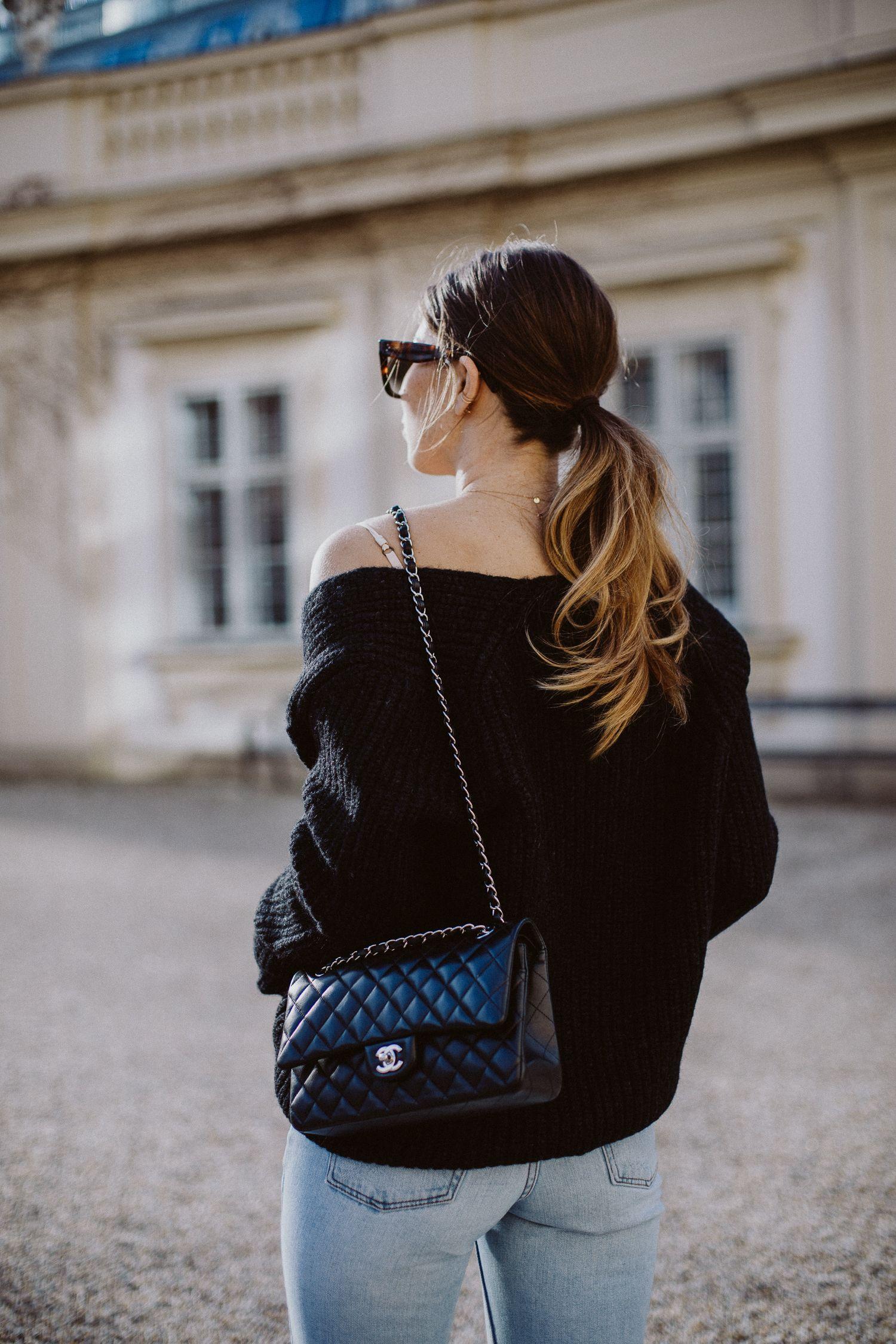 cô gái mặc áo đen tóc đuôi ngựa đeo túi Chanel classic flap bag