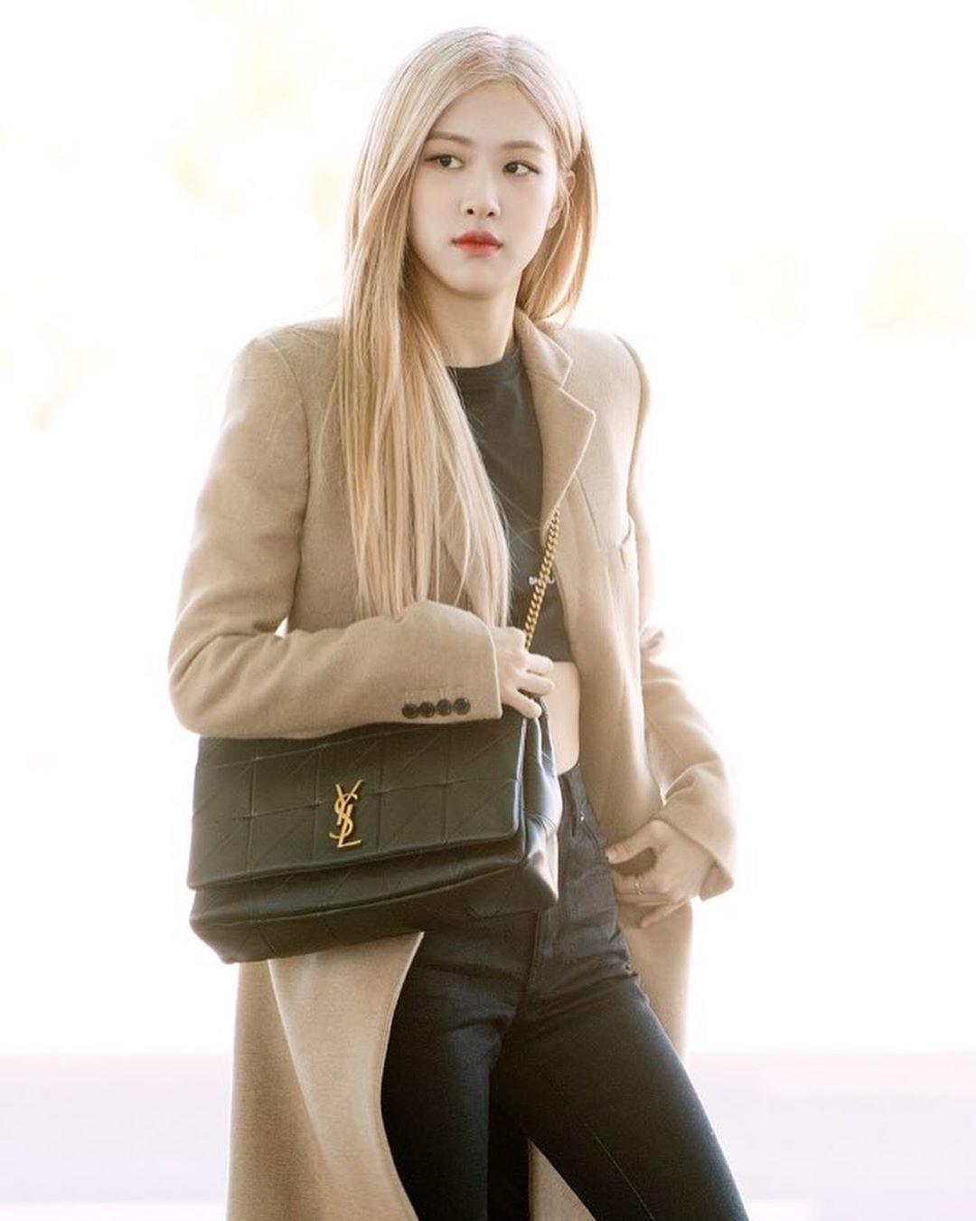 Rosé tóc vàng mặc áo khoác be áo đen quần đeo túi YSL