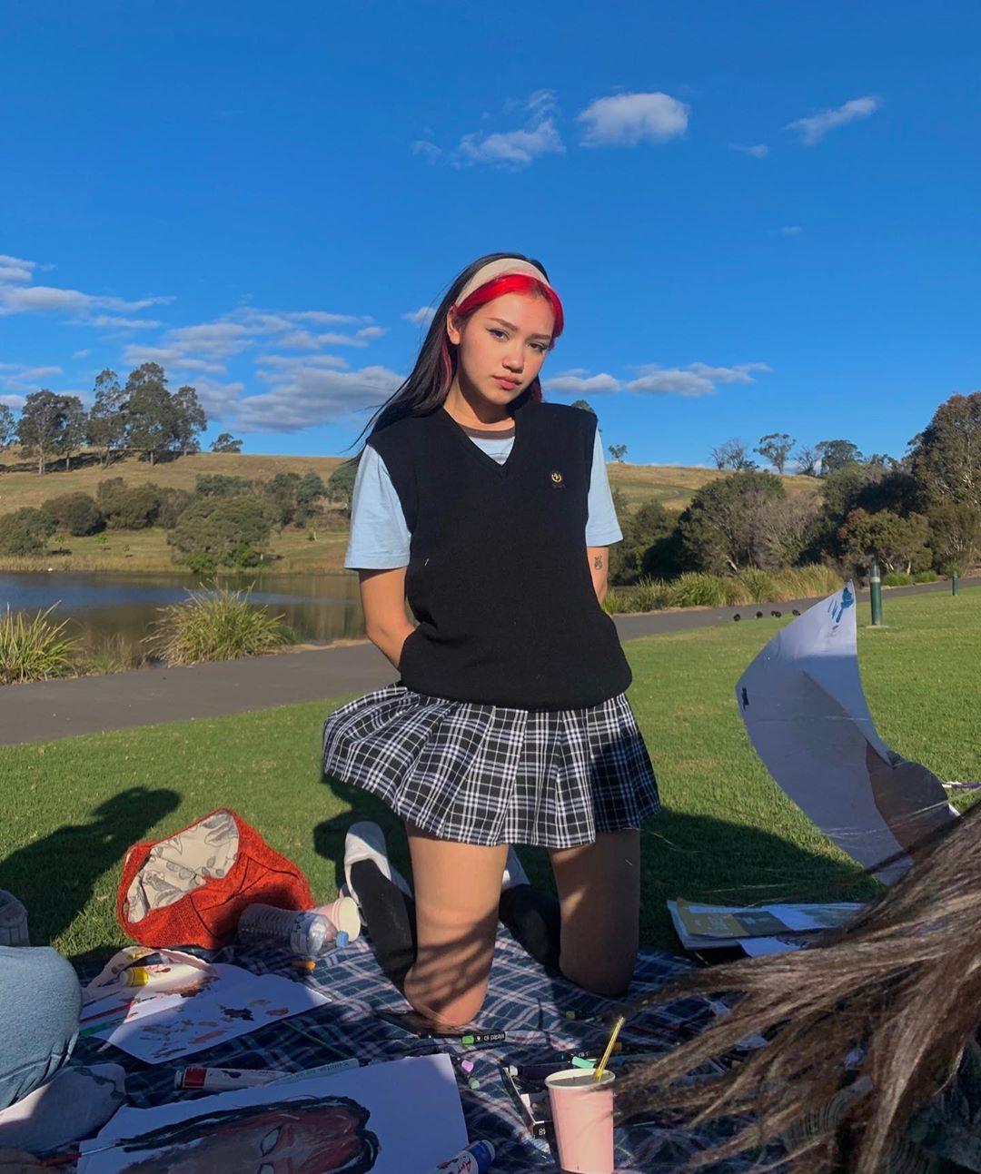 Áo thun phối cùng áo len gile và váy tennis Y2K