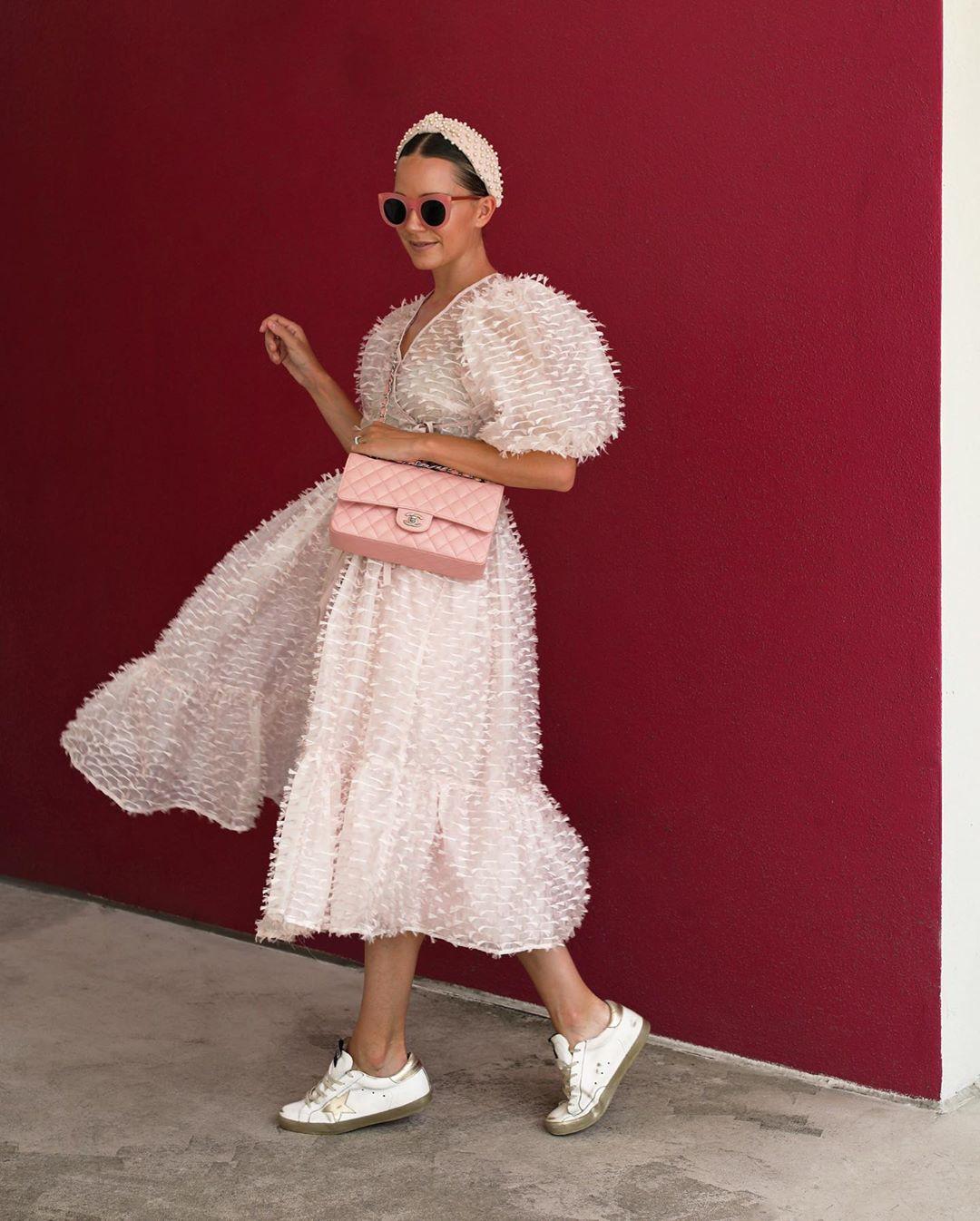 cô gái mặc váy hồng đeo mắt kính và túi xách chanel hồng