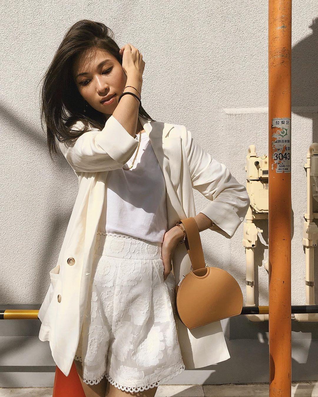 cô gái mặc full trắng đeo túi xách màu nâu