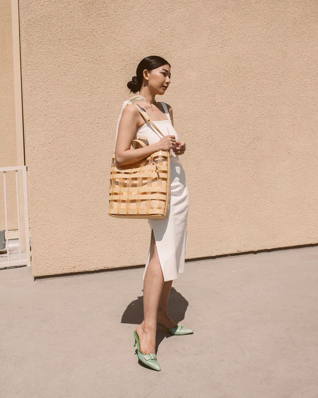 cô gái mặc váy hai dây trắng đeo túi xách oversize màu kem
