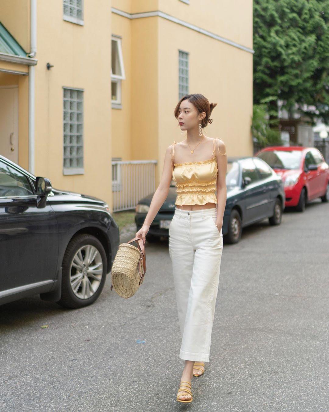 cô gái mặc áo dây lụa vàng quần trắng đeo túi xách cầm tay