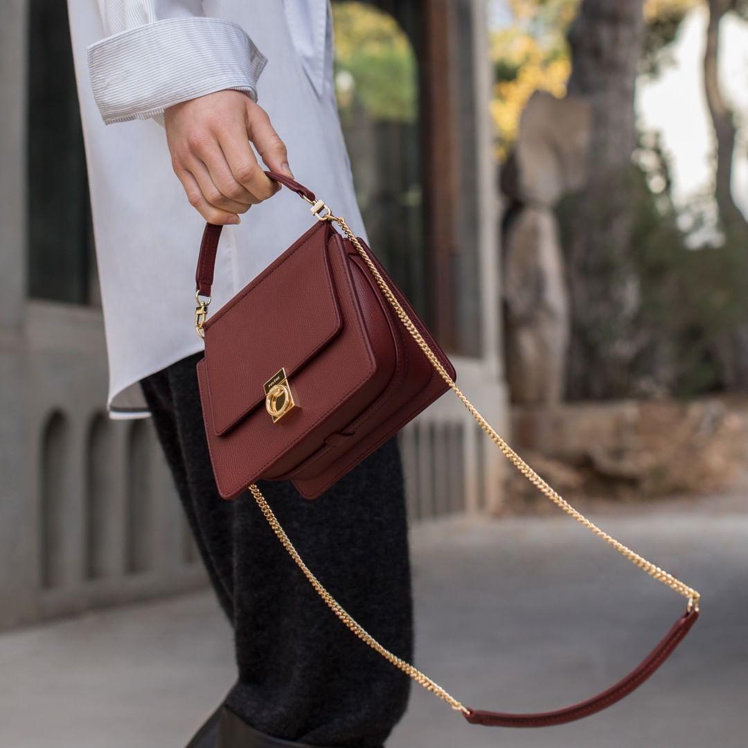 cô gái mặc sơ mi trắng quần đen cầm túi xách đỏ dây vàng