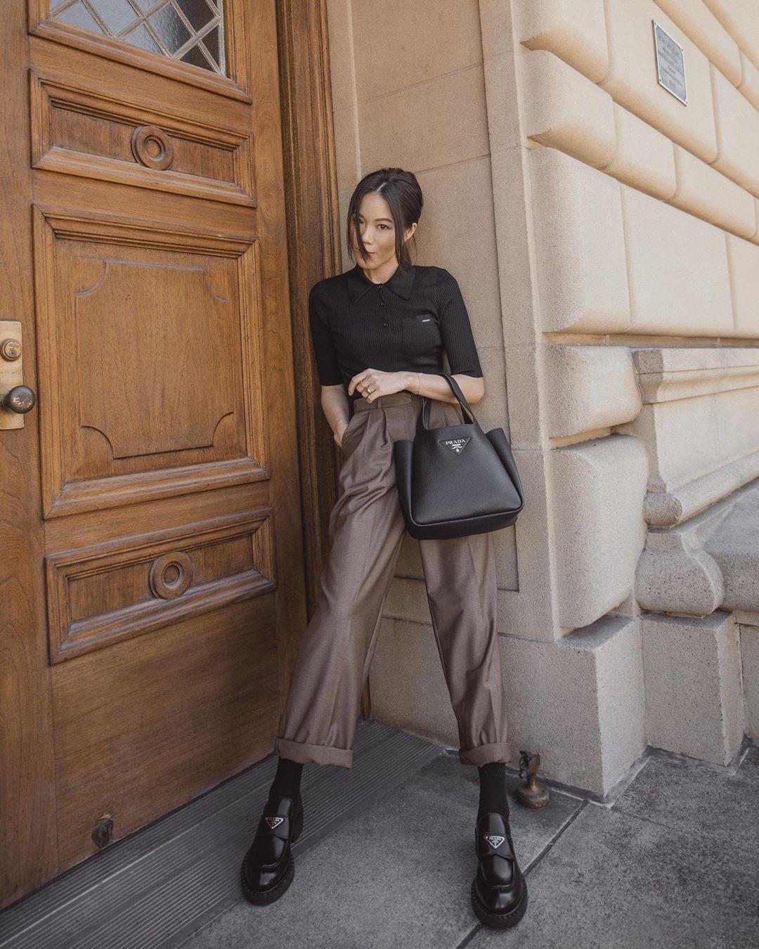 cô gái mặc áo đen quần nâu đeo túi xách đen