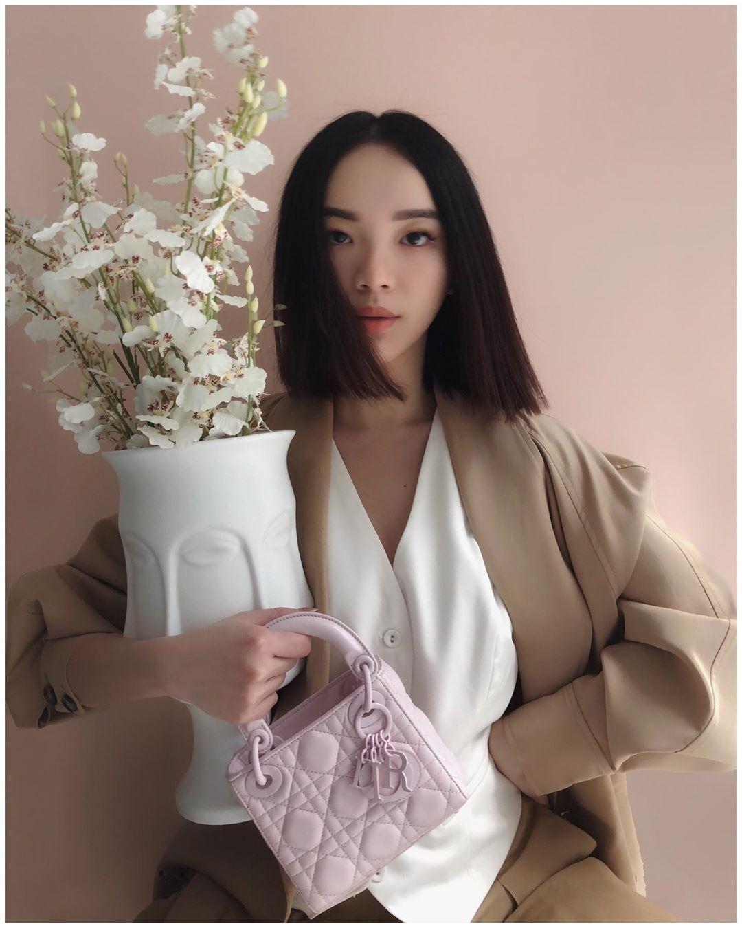 cô gái mặc áo trắng blazer nâu cầm bình bông đeo túi xách hồng dior