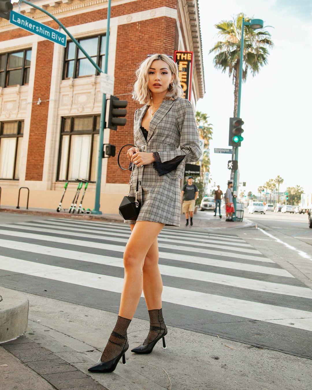 Cô gái phối đồ với váy blazer kẻ ô, giày vao gót đen và tất mỏng
