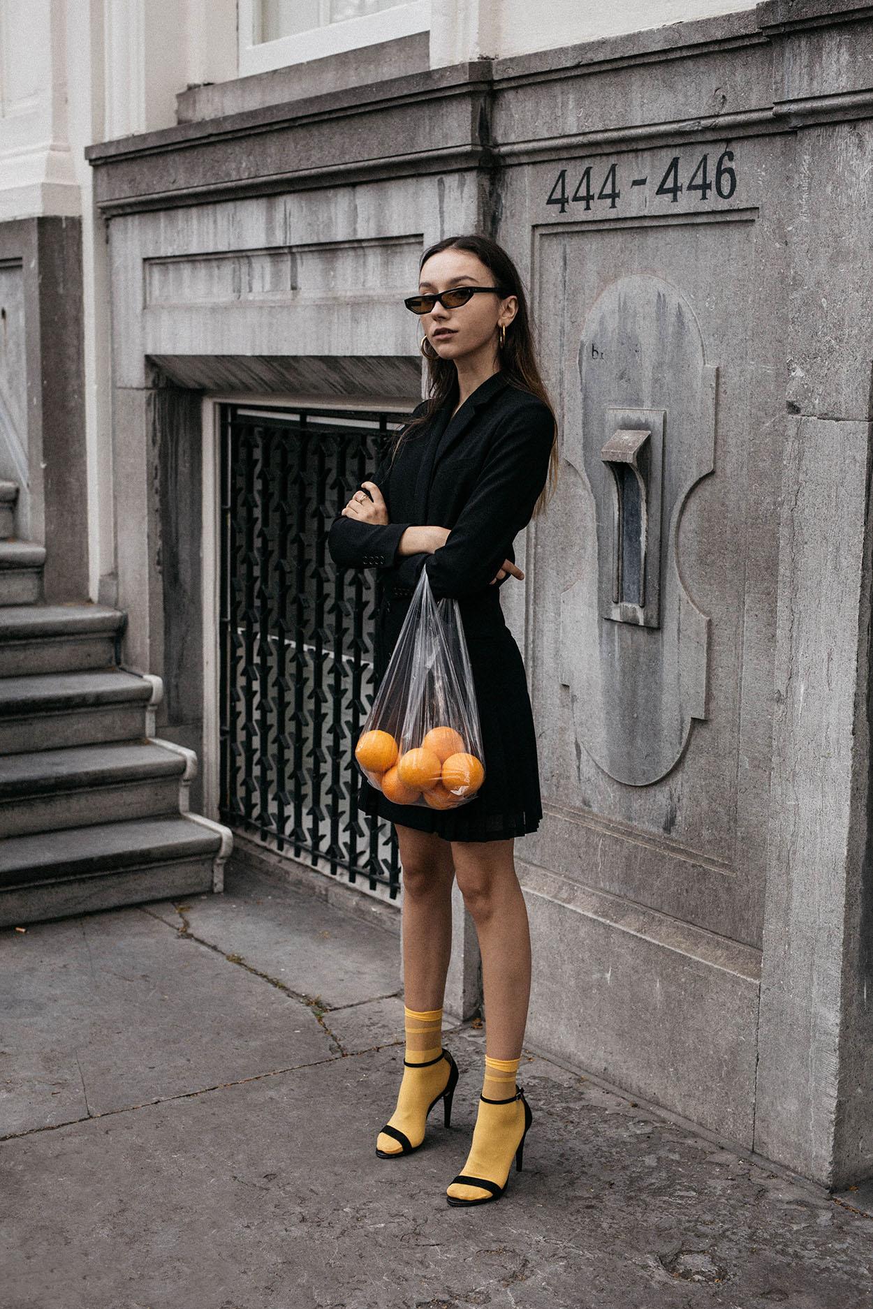 Cô gái phối đồ blazer váy màu đen với giày sandal cao gót và tất vàng