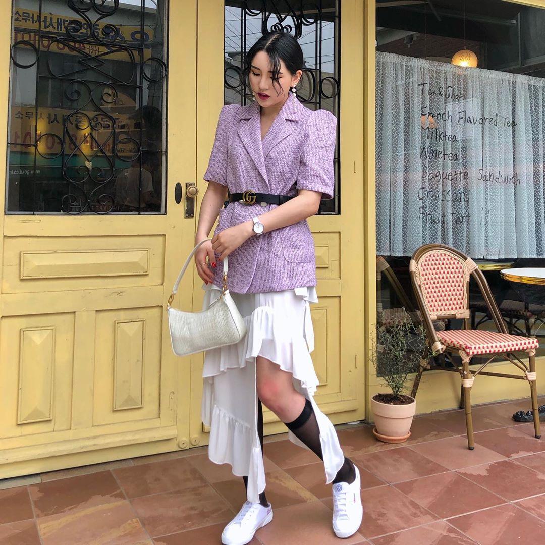 Cô gái phối đồ với chân váy bất đối xứng, giày sneakers trắng và tất lửng đen