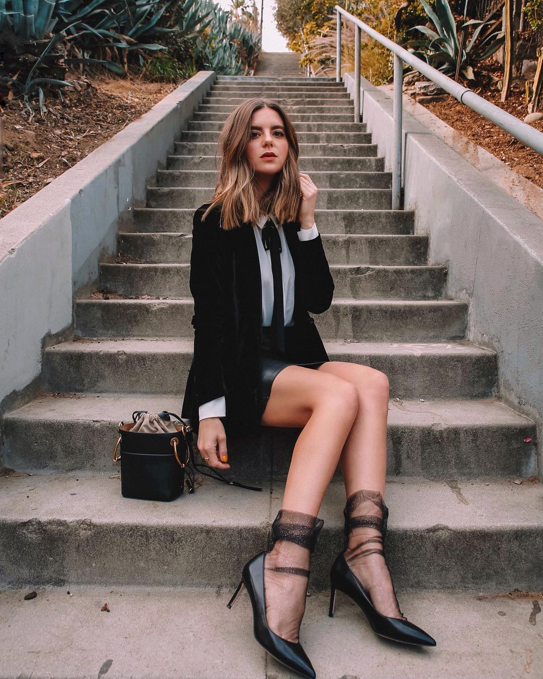 Cô gái phối đồ âu phục đen, giày cao gót đen và tất voan