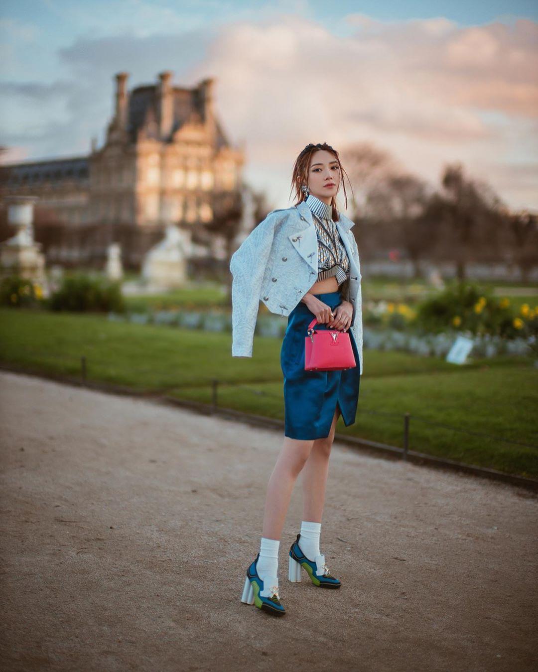 Cô gái phối đồ với chân váy xanh, áo khoác da, giày cao gót và tất trắng