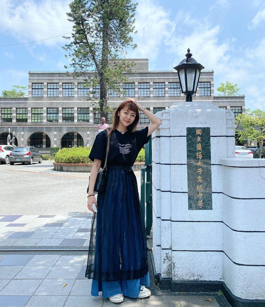 Cô gái phối đồ phong cách streetwear với áo thun đen, quần jeans rộng và chân váy xuyên thấu