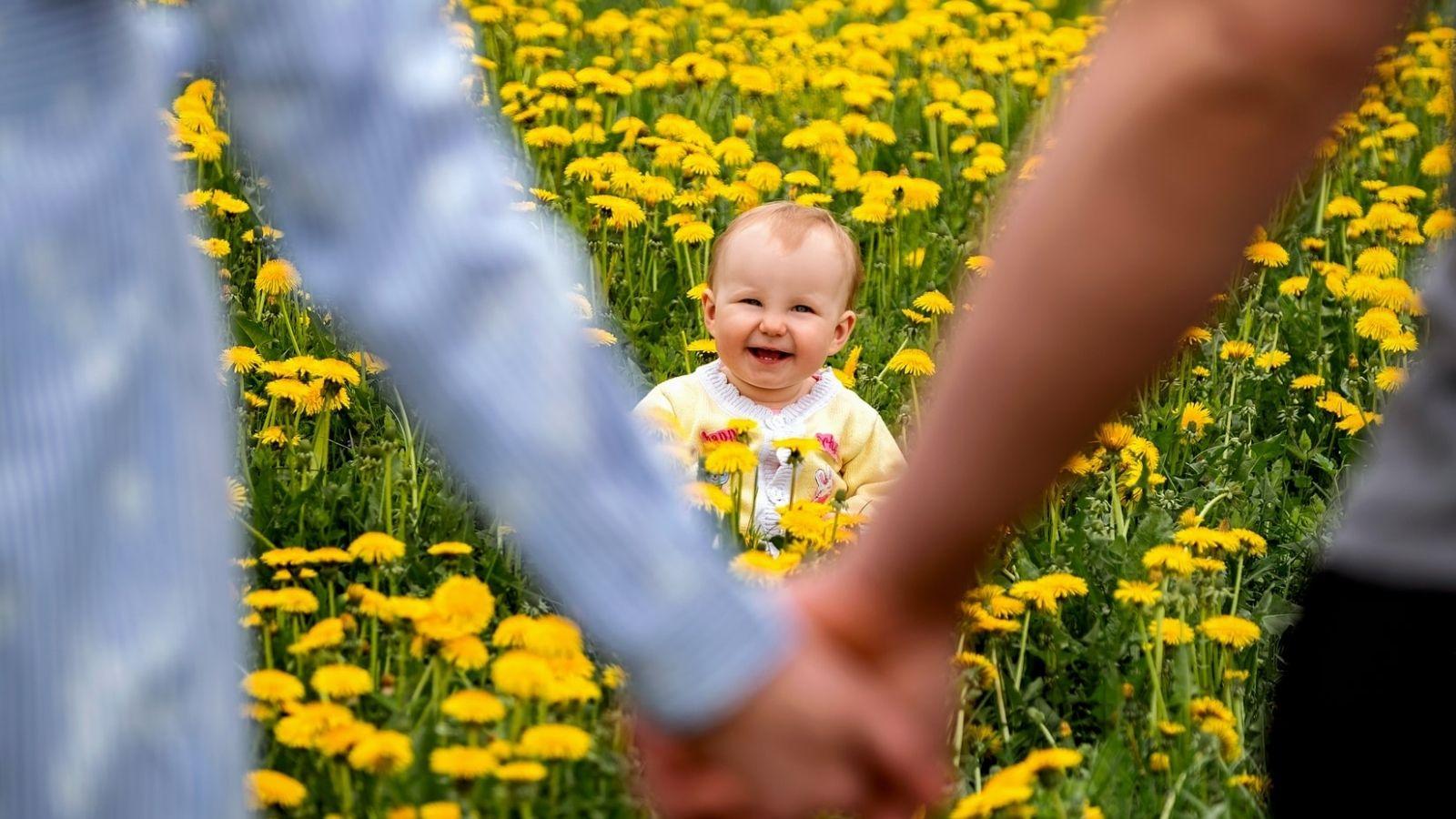 em bé tươi cười trong vòng tay ba mẹ