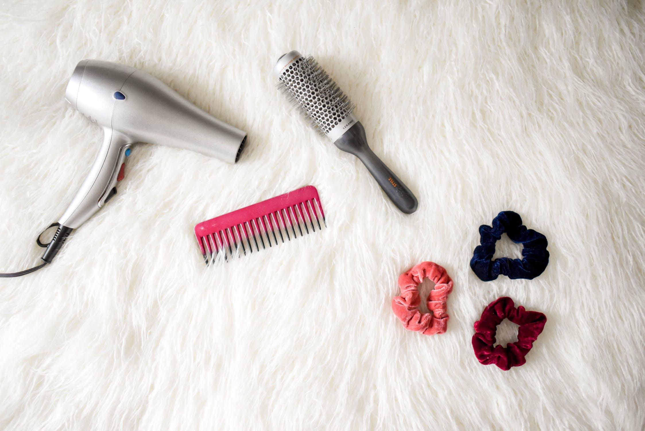 máy sấy tóc và lược trên giường