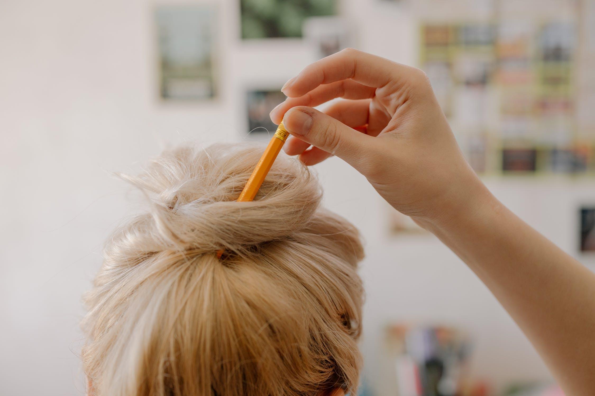 cô gái đang quấn tóc bằng bút chì