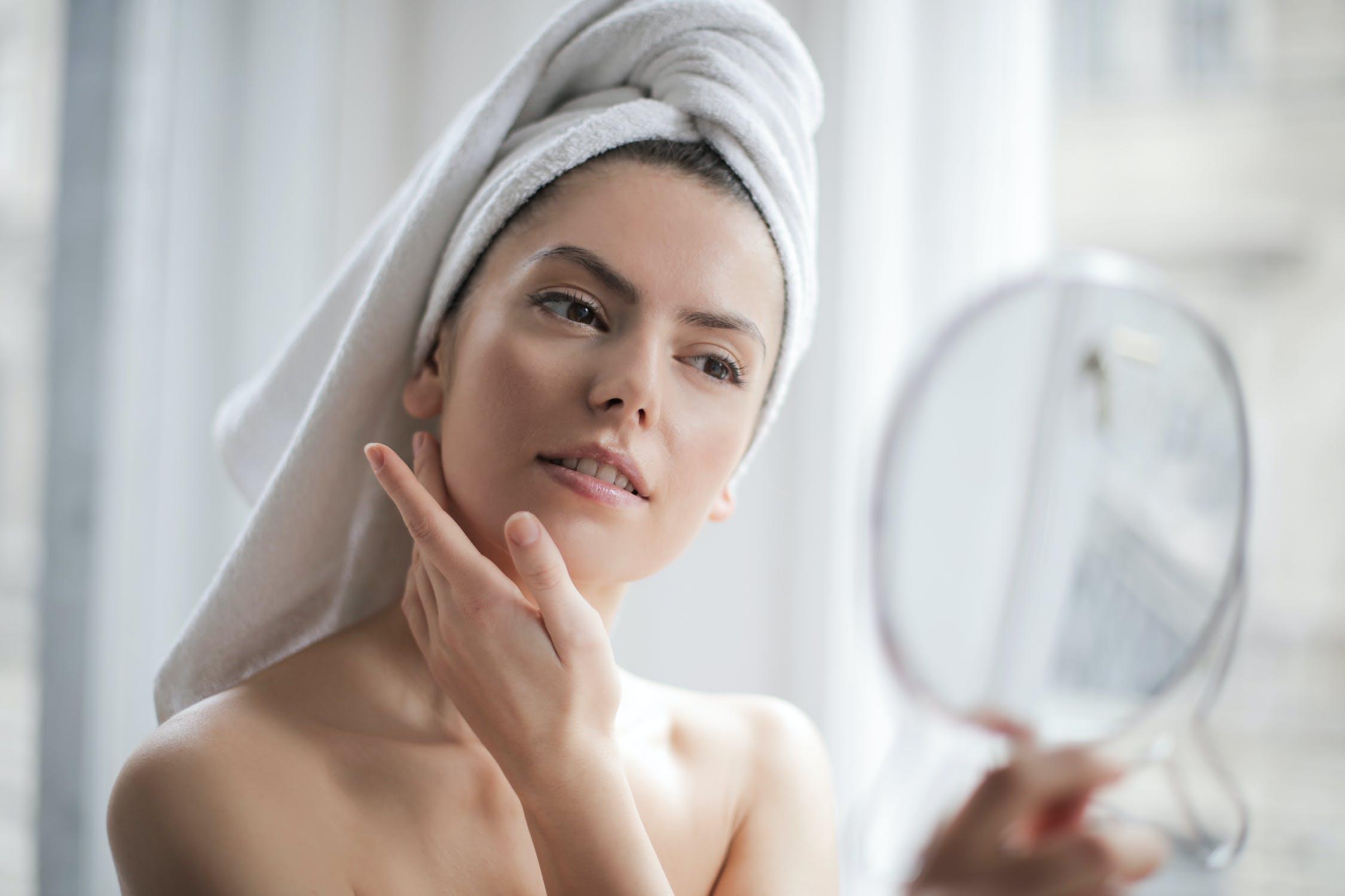 cô gái cầm gương sử dụng mặt nạ
