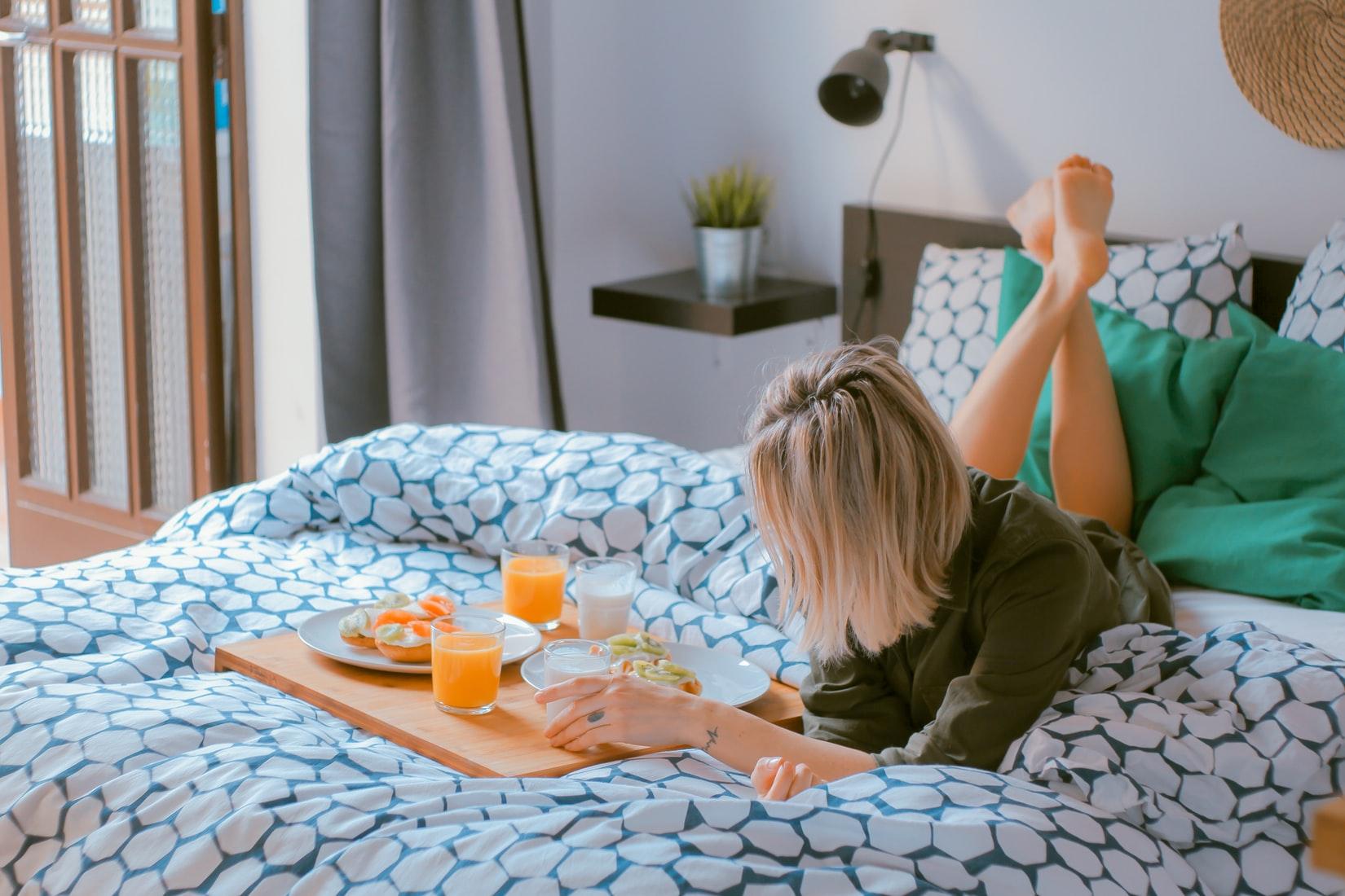 cô gái thư giãn bên cạnh bữa sáng trên giường sau giấc ngủ