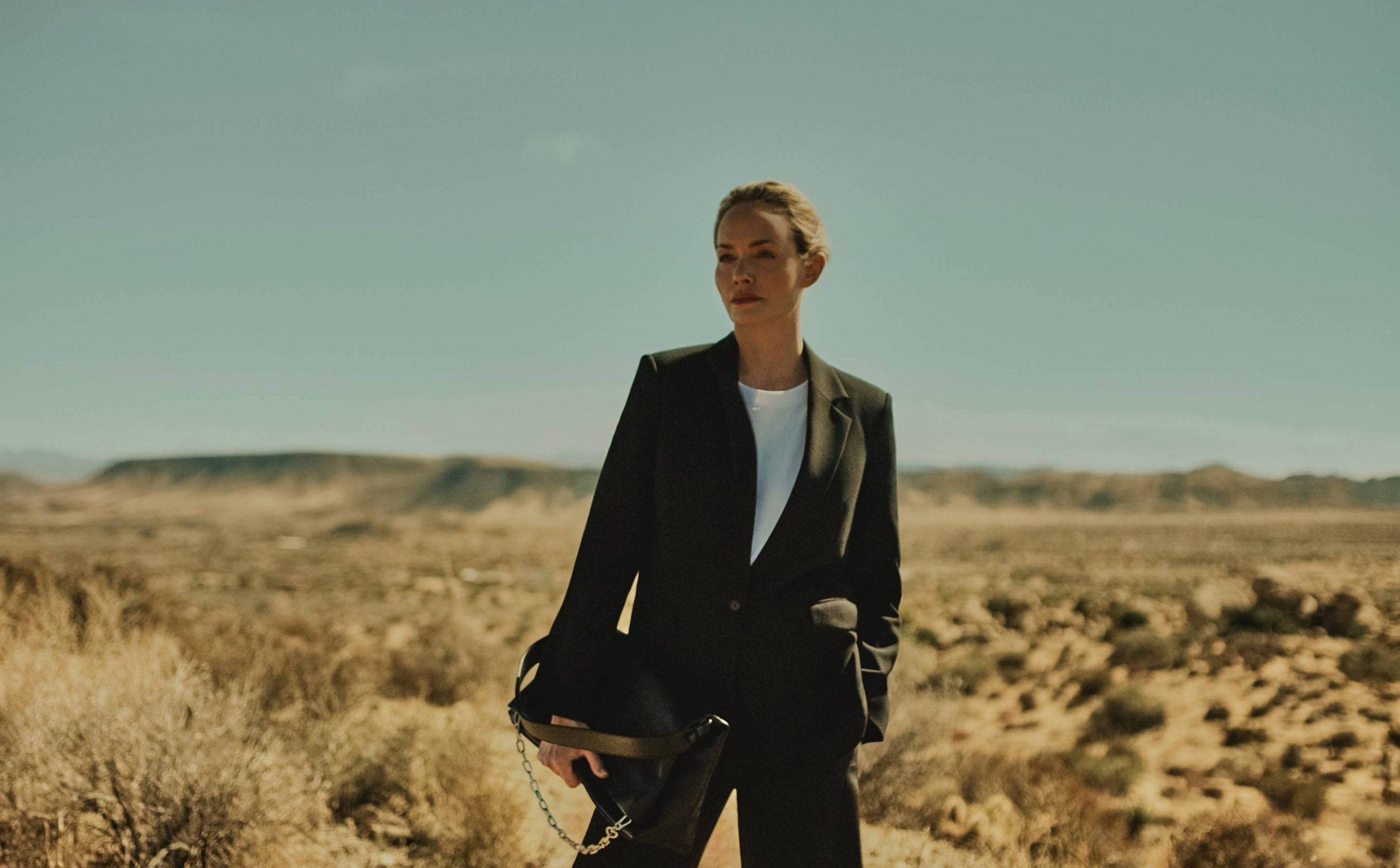 Amber Valletta in black suit holding black cactus leather K:Kushion from the collaboration campaign with Karl Lagerfeld
