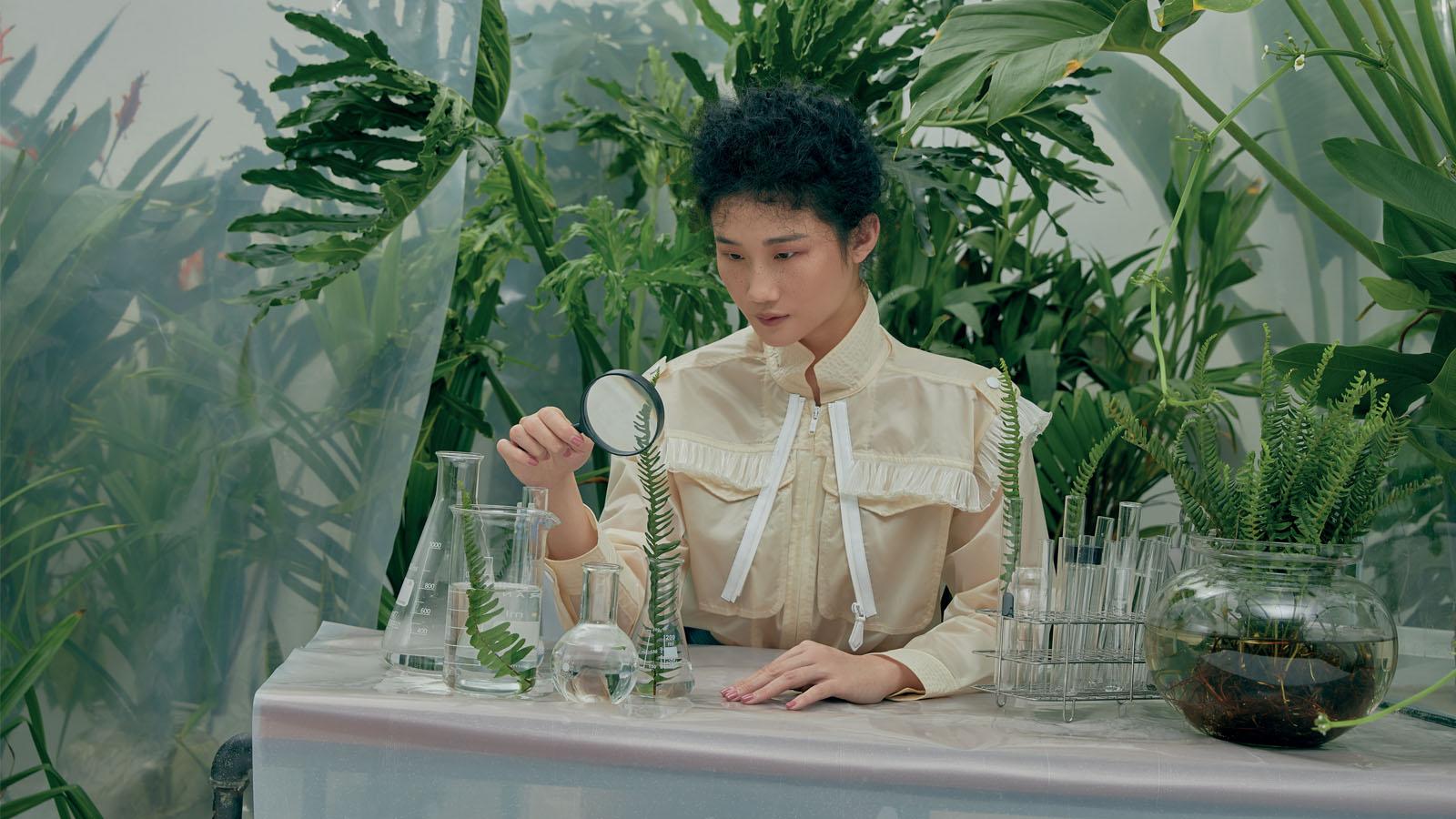 cô gái cầm kính lúp soi cây bền vững