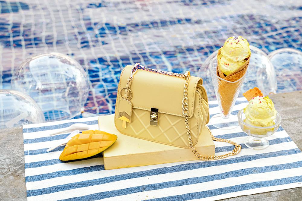 Túi Juno bag đeo chéo màu vàng pastel chụp tại hồ bơi