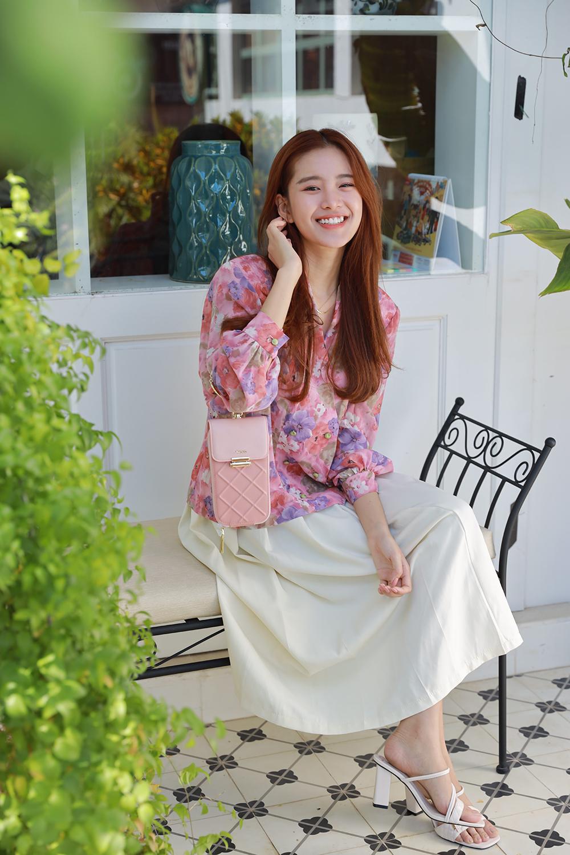 Trâm Ngô cùng túi clutch hồng Juno và sandals trắng