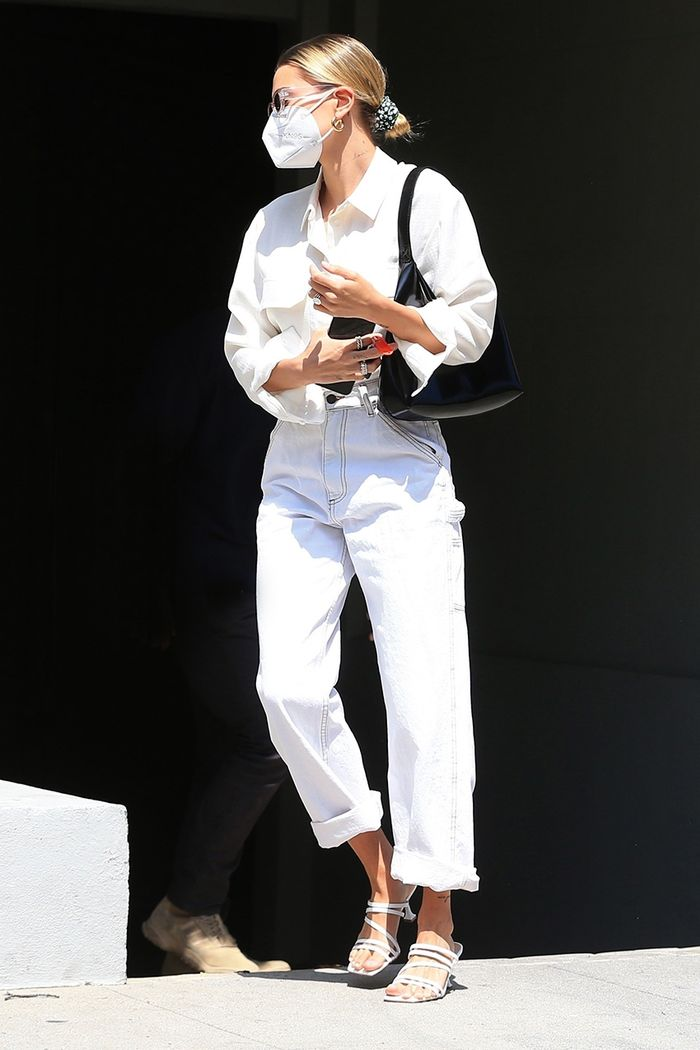 Hailey Bieber is out in a white outfit and hair in a bun.